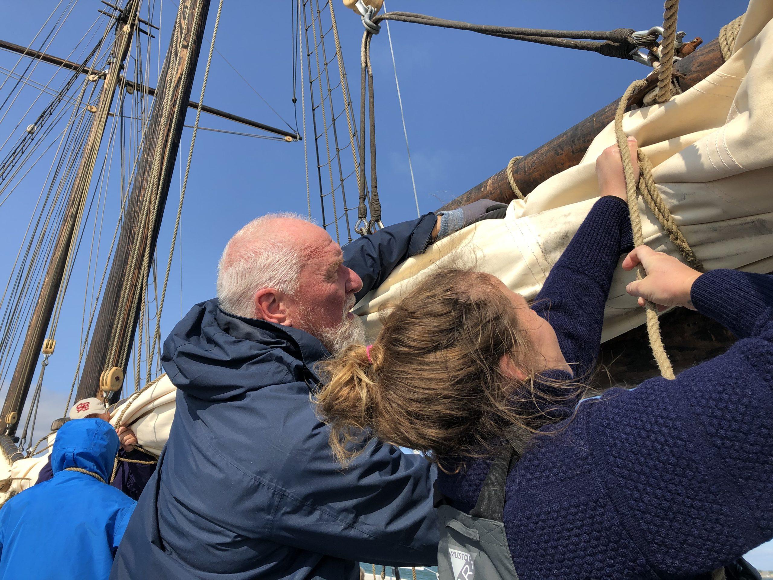 Venner og besætning hjælper hinanden med at pakke sejlet